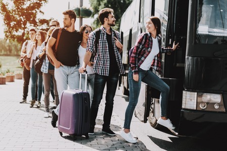Group of Young People Boarding on Travel Bus. Happy Travelers Standing in Queue Holding Luggage Waiting their turn to Enter Bus. Traveling, Tourism and People Concept. Summer Vacation Stok Fotoğraf