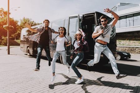 ツアーバスの前で飛び跳ねる興奮した若者たち。一緒にジャンプして笑うバックパックと笑顔の友人のグループ。旅行、観光、人々のコンセプト。 写真素材