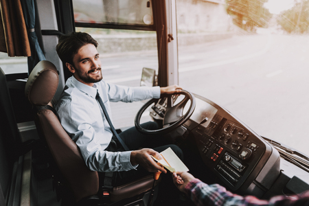 Smiling Young Driver taking Ticket from Passenger. Handsome Happy Man wearing Blue Shirt Sitting on Driver Seat of Tour Bus. Attractive Confident Man at Work. Traveling, Transport and Tourism Concept Stock Photo