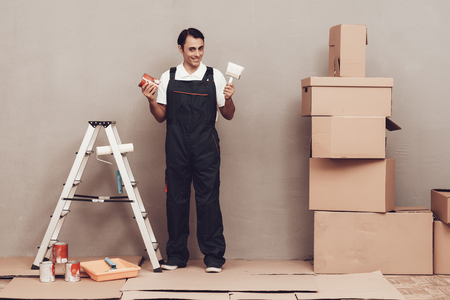 Master Painter. Gray Wall. Cardboard Boxes and Construction Ladder. Man in Uniform. Master Painter with Paint and Brush in Hand. Painting Walls. Repair Home. Gray Background.