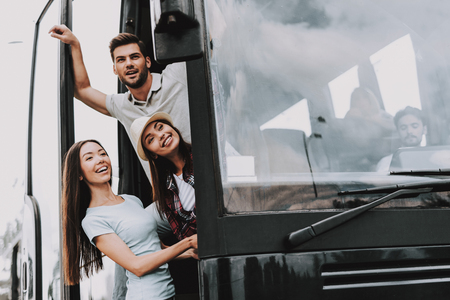 Young Smiling People Traveling on Tourist Bus. Group of Happy Friends Standing Together in Doors of Tour Bus. Traveling, Tourism and People Concept. Happy Travelers on Trip. Summer Vacation Imagens