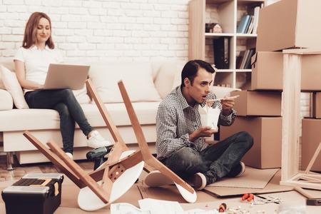 Assemble Furniture. Man Repairing Chair. Man with Furniture Instructions. Furniture Assembler Have Working Break. Woman on Sofa with Laptop. Master Eats Lunch on Floor. Eats Lunch on Floor in Room.