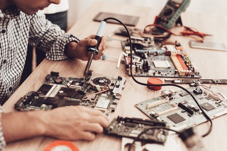 Meister-Gadgets. Geräte reparieren. Meister mit Lötlampe Bewertungen. Ersatzteile und Geräte auf dem Tisch. Mann macht Reparaturen am Tisch. Technik auf dem Tisch. Servicemitarbeiter. Lötlampe Bewertungen und Technik.