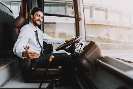 Smiling Man Driving Tour Bus. Professional Driver. Young Happy Man wearing White Shirt and Black Tie Sitting on Driver Seat. Attractive Confident Man at Work. Traveling and Tourism Concept Archivio Fotografico