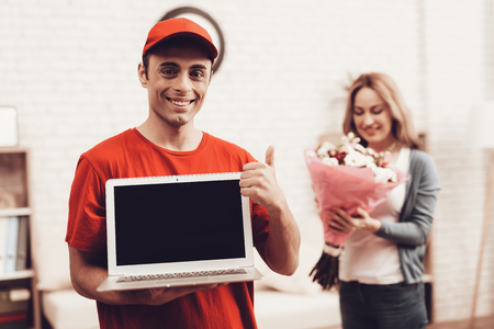 Courier Delivery. Man Deliveryman with Laptop. Smiling Worker Man Arab Nationality. White Interior. Deliveryman Arab Nationality. Courier in Orange Clothes. Express Delivery. Smiling Girl Flowers.