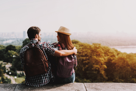 Young Couple Sitting on Ledge and Looking at Park. Young Man and Woman with Backpacks Sitting Together on Concrete Ledge. Couple Enjoying Beautiful View of Nature. Traveling Concept