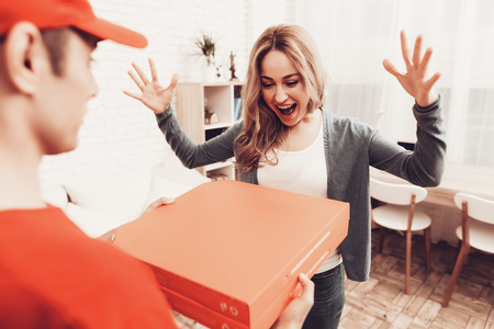Pizza Delivery. Pizza Deliveryman. Girl with Pizza. Man with Box is Funny Accessory. White Interior. Deliveryman Arab Nationality. Courier in Orange Clothes. Fast Food. Express Delivery. Happy Woman.