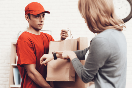 Courier Delivery. Arab Deliveryman. Woman with Package. White Interior. Deliveryman Arab Nationality. Courier in Orange Clothes. Express Delivery. Gives Paper Package. Paper Package. Clock on Arm.