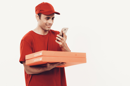 Courier Delivery. Man Deliveryman Looks in Phone. Worker Man Arab Nationality. White Interior. Deliveryman Arab Nationality. Courier in Orange Clothes. Express Delivery. Courier on White Background.