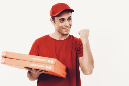 Courier Delivery. Man Deliveryman with Pizza. Worker Man Arab Nationality. White Interior. Deliveryman Arab Nationality. Courier in Orange Clothes. Express Delivery. Courier on White Background.