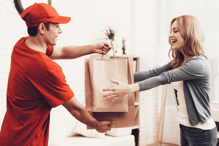 Courier Delivery. Man Deliveryman. Worker Man Arab Nationality. White Interior. Deliveryman Arab Nationality. Courier in Orange Clothes. Express Delivery. Gives Paper Package. Paper Package.