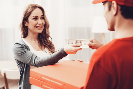 Pizza Delivery. Pizza Deliveryman. Man with Box is Accessory. White Interior. Deliveryman Arab Nationality. Courier in Orange Clothes. Woman with Courier. Express Delivery. Pizza Delivery Payment. Stock Photo