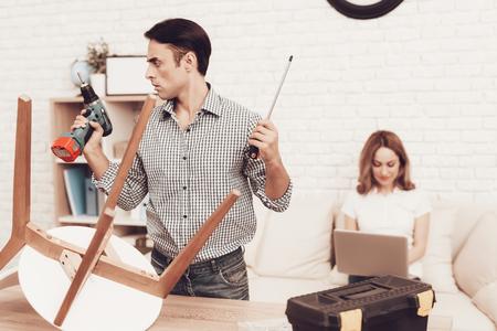 Assemble Furniture. Man Repairing Chair. Man Collects Chair. Furniture Assembler with Drill. Woman on Sofa with Laptop. Craftsman with Tools Repairs Chair. Furniture Repair. Looking Drill in Hand.