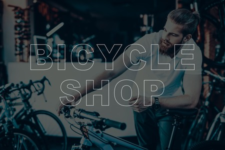 Bicycle Shop. Man Using the Bicycle. Guy Checks the Bike. Man Looking on His Bicycle. Young Beard Man. Hipster Man. Different Bicycles on Background of Man. Man Sales the Bicycles.