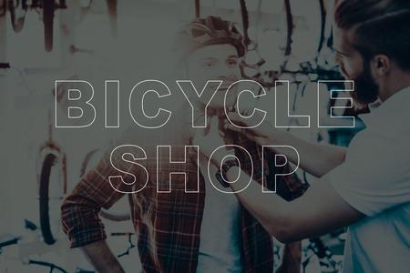 Bicycle Shop. Customer Choosing the Helmet on His Bike. Buyer Wearing a Helmet. Salesman Helping to Customer. Customer Measures a Helmet. Customer Smiling. Different Bikes on Background of Man.