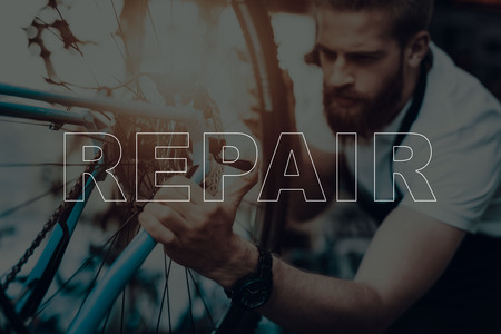 Bicycle Shop. Bicycle Repair. Salesman Using a Bicycle. Bicycle is Broken. Salesman Using Pedal of Bicycle. Pedal on Wheel on Bicycle. Man Looking on Bike. Different Bicycles on Background.