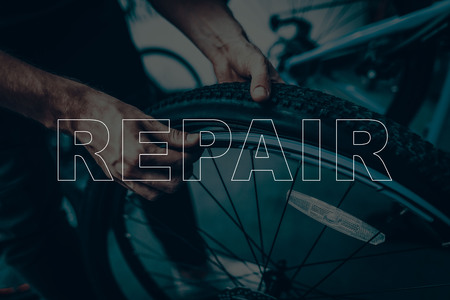 Bicycle Shop. Bicycle Repair. Salesman are Using a Bicycle. Tyre Wheel on Bicycle is Broken. Salesman are Changing a Tyre. Different Bicycles on Background. Closeup View. Male Worker.
