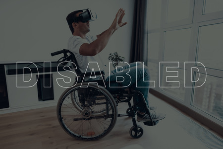 Disabled Man in a Wheelchair. Man Sits in Front of Window. Man Wearing a Virtual Reality Glasses. Man is Gesticulating of Hands. Man is Surprised. Man is Located in Living Room. Virtual Technologies.