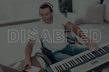 Disabled Man in a Wheelchair. Man Sitting at Table. Man Playing a Music on Synthesizer. Man Typing on Laptop. Man Wearing Headphones. Man is Smiling. Adult Man. Man is Located in the Living Room. Imagens