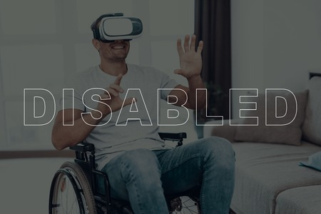 Disabled Man in a Wheelchair. Man Wearing a Virtual Reality Glasses. Man is Gesticulating of Hands. Man is Smiling. Adult Brunette Man. Man is Located in the Living Room. Virtual Technologies. Banco de Imagens