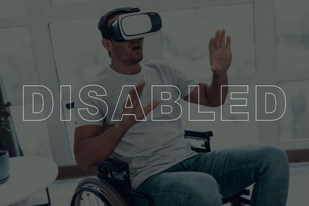 Disabled Man in a Wheelchair. Man Wearing a Virtual Reality Glasses. Man is Gesticulating of Hands. Man is Surprised. Adult Brunette Man. Man is Located in the Living Room. Virtual Technologies.