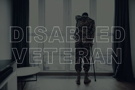Military Veteran. Man Standing and Touching the Window. Large Panoramic Window. Man with Crutch. Man is Soldier. Soldier in Military Uniform. Man is Sad. Man Located in the Living Room. Imagens