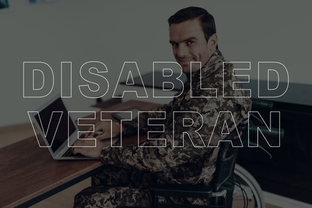 Military Veteran. Disabled Man in a Wheelchair. Man Sitting at Table. Man Using Laptop. Man is Soldier. Soldier in Military Uniform. Man Looking into Camera. Man Smiling. Man Located in the Living Room. Imagens