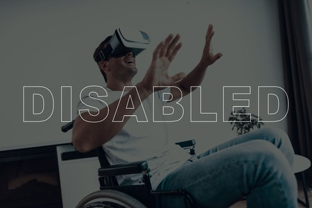 Disabled Man in a Wheelchair. Man Wearing a Virtual Reality Glasses. Man is Gesticulating of Hands. Man Smiling. Adult Brunette Man. Man is Located in the Living Room. Virtual Technologies.