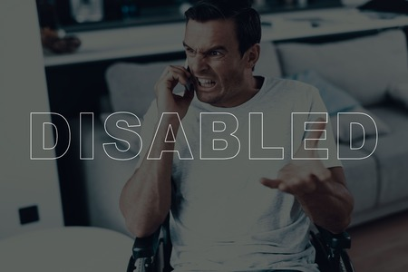 Disabled Man in a Wheelchair. Man Talking on Mobile Phone. Man Have Call on Smartphone. Man is Angry. Man is Gesticulating of Hand. Adult Brunette Man. Man Located in the Living Room.