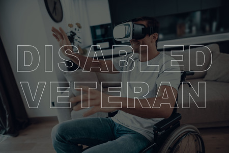 Disabled Man in a Wheelchair. Man Wearing a Virtual Reality Glasses. Man is Gesticulating of Hands. Adult Brunette Man. Man Smiling. Man is Located in the Living Room. Virtual Technologies.