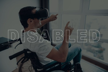 Disabled Man in a Wheelchair. Man Sits in Front of Window. Man Wearing a Virtual Reality Glasses. Man is Gesticulating of Hands. . Man Smiling. Man is Located in the Living Room. Virtual Technologies. Imagens