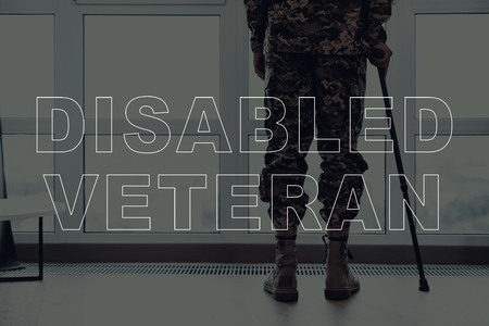 Military Veteran. Man Standing in Front of Window. Large Panoramic Window. Man with Crutch. Man is Soldier. Soldier in Military Uniform. Man Looking into Window. Man Located in the Living Room.