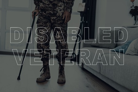 Military Veteran. Man is Walking in Front of Window. Large Panoramic Window. Man with Crutch. Man is Soldier. Soldier in Military Uniform. Man Located in the Living Room. Down View. 스톡 콘텐츠