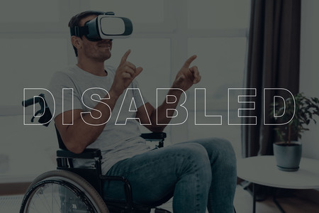 Disabled Man in a Wheelchair. Man Wearing a Virtual Reality Glasses. Man is Gesticulating of Hands. Man is Smiling. Adult Brunette Man. Man is Located in the Living Room. Virtual Technologies. Imagens