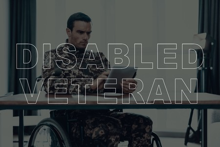 Military Veteran. Disabled Man in a Wheelchair. Man Sitting at Table. Man Using Tablet PC. Man is Soldier. Soldier in Military Uniform. Man is Serious. Man Located in the Living Room.