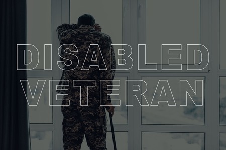 Military Veteran. Man Standing and Touching the Window. Large Panoramic Window. Man with Crutch. Man is Soldier. Soldier in Military Uniform. Man is Sad. Man Located in the Living Room. Standard-Bild