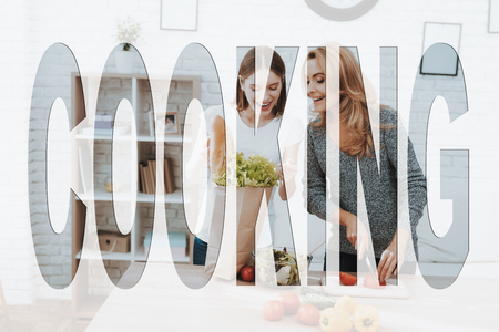 Family Cooking. Mother and Daughter Cooking in Kitchen. Mother and Daughter Cooking a Salad. Salad from Fresh Vegetables. Daughter Showing Bag with Products to Mother. Mother Cutting a Tomatoes. Banco de Imagens
