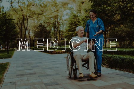 Smiling People. Man Show Something on Tablet. Retirement in Nursing Home. Man and Doctor Ride on Walkway. Outdoor Rehabilitation. Good Medicine in Nursing Home. Old Man in Wheelchair.