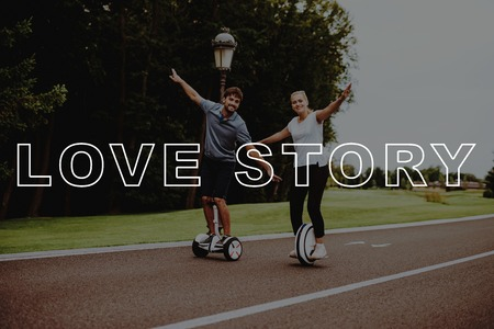 Couple Love Story. Young People Hold Arms Apart. Pair Riding Gyro scooter and Monocle. Pair in Country Park. Young People Happy Together in Park. Smiling People Have Fun. Romantic Relationships. Stock Photo