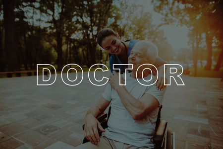 Doctor Leaned Toward Patient. People Walk in Sunset. Outdoor Rehabilitation. Man Sit in Wheelchair. Good Medicine in Nursing Home. Disabled in Wheelchair. Smiling Old Man in Park. Man Retirement.