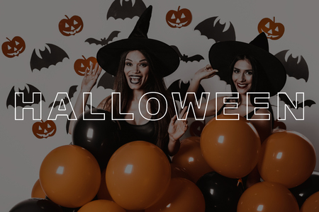 Lady on Halloween Party Hold Orange Balloons. Halloween Makeup. Party in Magic Studio. Women in Black Dresses. Joyful Girls. Suits Witches. Slender Two Women Smile. Pretty Girls in Gothic Look.