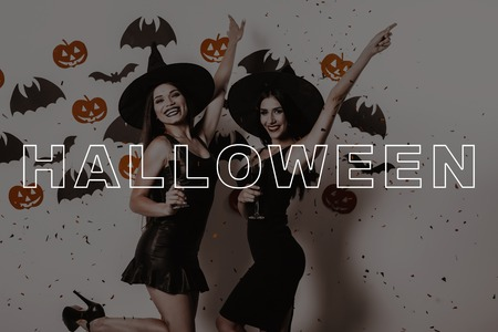 Girls with Halloween Makeup. Suits Witches. Confetti Flashes. Lady on Halloween Party. Women with Glasses of Wine Smile. Women in Black Dresses. Party in Magic Studio. Laugh Girls. Pretty Gothic Look.