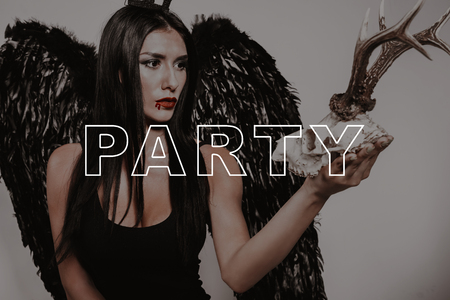 Halloween Party. Young Woman Hold Deer Skull. Lady in Black Tight-Fitting Dress. Demon Suit Girl. Gothic Look. Dark Hair Super Sexy Girl. Glamour Lady in Magic Studio. Halloween Fashion Posing. Imagens