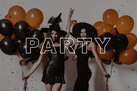 Joyful Girls Hold Orange Balloons. Halloween Makeup. Lady on Halloween Party. Suits Witches. Slender Two Women Smile. Women in Black Dresses. Party in Magic Studio. Pretty Girls in Gothic Look.