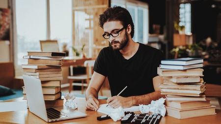 Pensive Freelance Text Writer Working at Desk. Pensive Handsome Hardworking Freelance Screenwriter Scenarist Sits Near Big Stacks of Books Writing Article, Novel, Play on Paper Sheets Looks Away