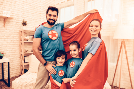 Portrait of Cute Smiling Super Hero Family at Home. Smiling Parents with Children Sitting on Sofa at Home. Stok Fotoğraf