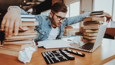 Concentrated Freelance Writer Working at Desk. Overworked Pensive Handsome Hardworking Screenwriter Scenarist Sits Near Big Stacks of Books Writing Article, on Paper Sheets. Lack of Ideas Concept