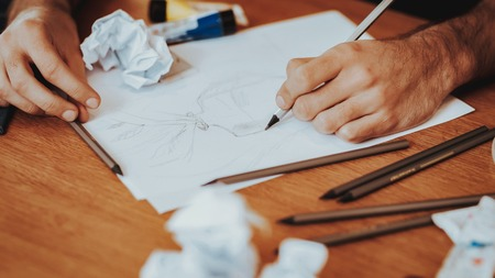 Closeup of Artist Desktop with Papers and Brushes. Male Hands Holding Pencil Drawing on Wooden Table. Painting Stuff Lying at Desktop Items. Creative Art Hobby and Artist Tools Concept