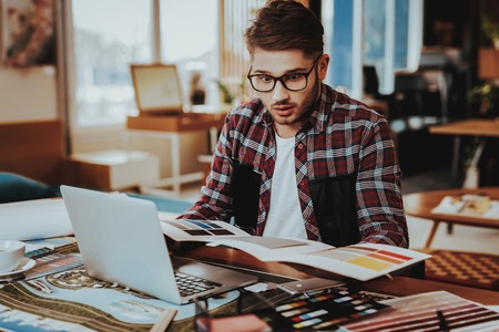 Suprised Designer Frowns While Working at Project. Portrait of Stressed Stylish Graphic Illustrator Sits at Table Holds Colorful Palette at Workplace. Creative Distance Job Concept Stock Photo