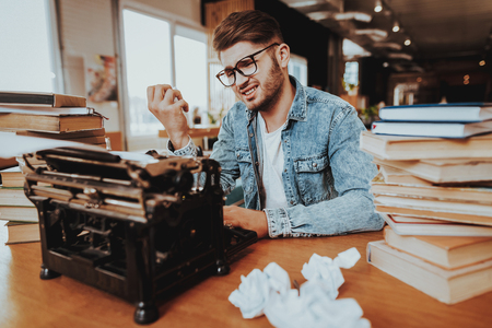 Nervous Sad Textwriter Working on Typewriter. Pensive Handsome Hardworking Freelance Screenwriter Scenarist Sits Near Stacks of Books Writing Play. Antique Retro Style of Work. Lack of Ideas